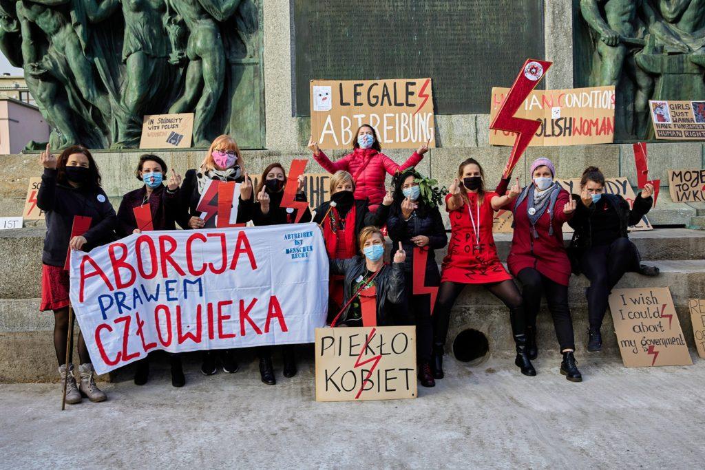 Zdjecie z demostracji, grupa kobiet ubranych na czarno i czerwono z transparentami i blyskawicami.